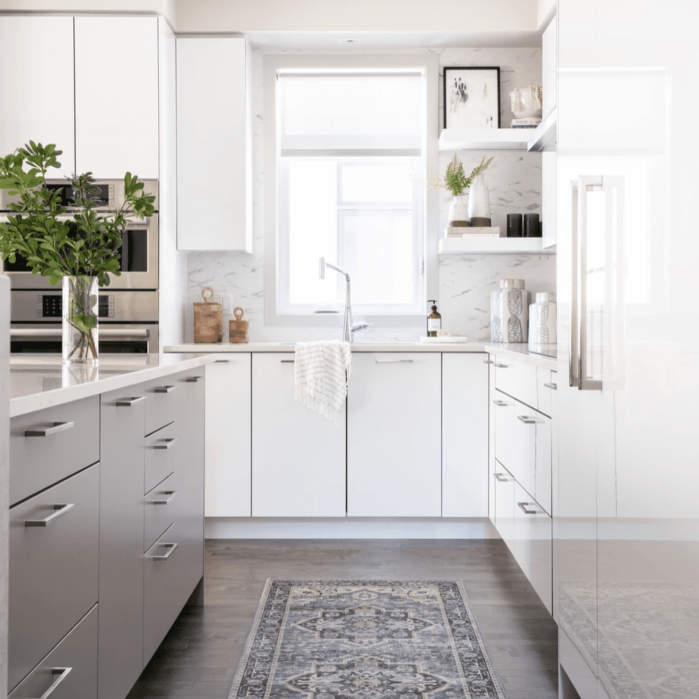 A kitchen with white and gray cabinets