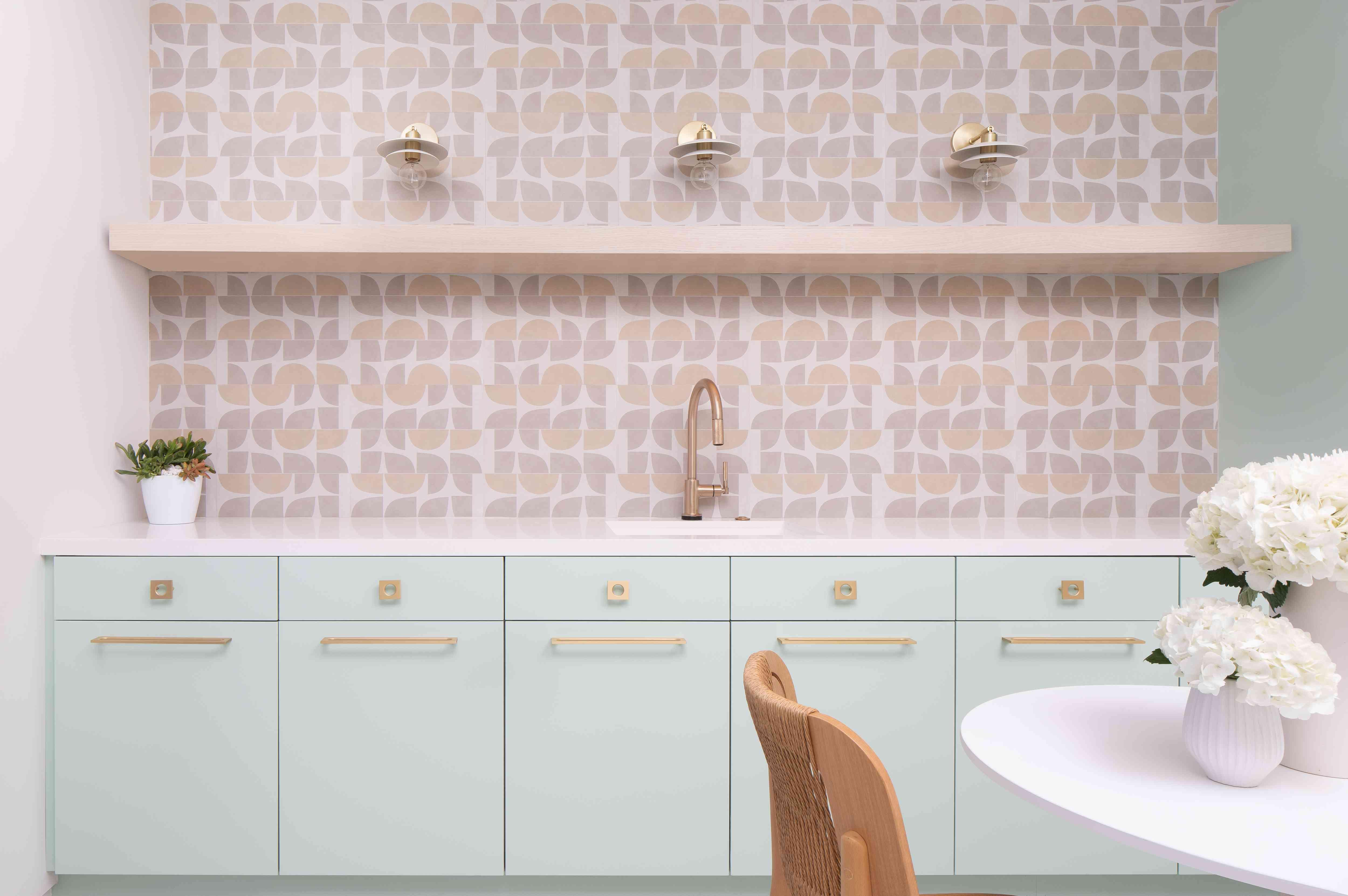 Mint green cabinets and pink tile backsplash.