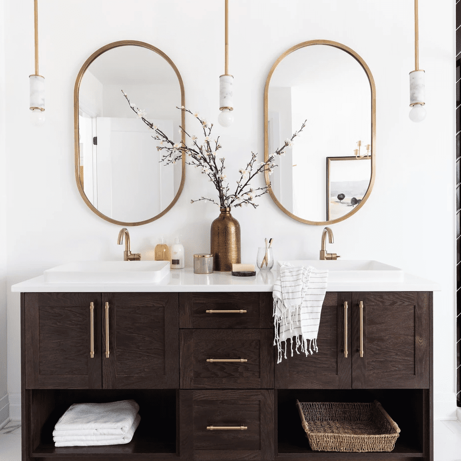 A double vanity framed by several gold pendant lights
