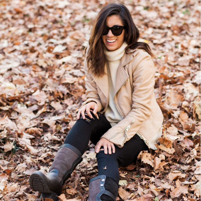 a woman sitting in fall leaves