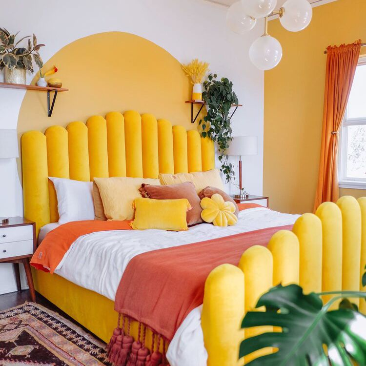 A vibrant bedroom with warm yellow walls