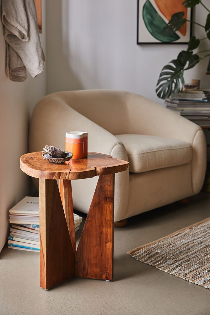 A live-edge wood side table in a decorated room