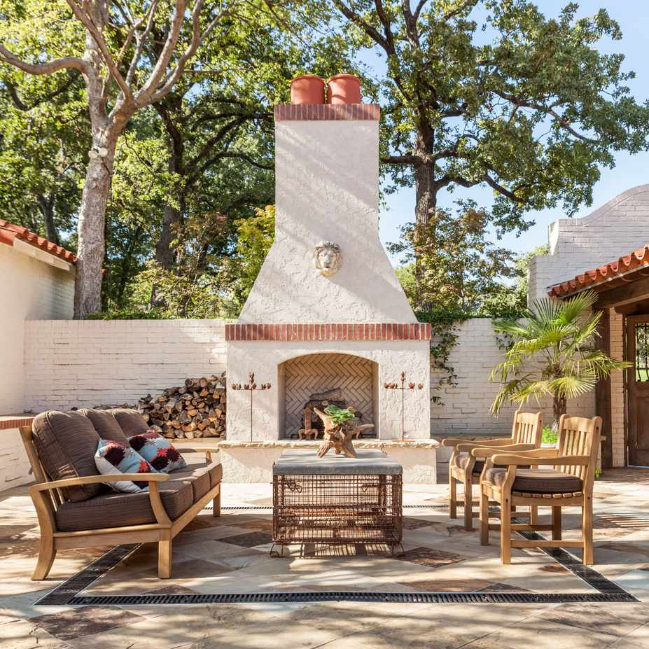 An outdoor fireplace made from white stucco and red bricks, attached to a home made from white bricks and red stucco