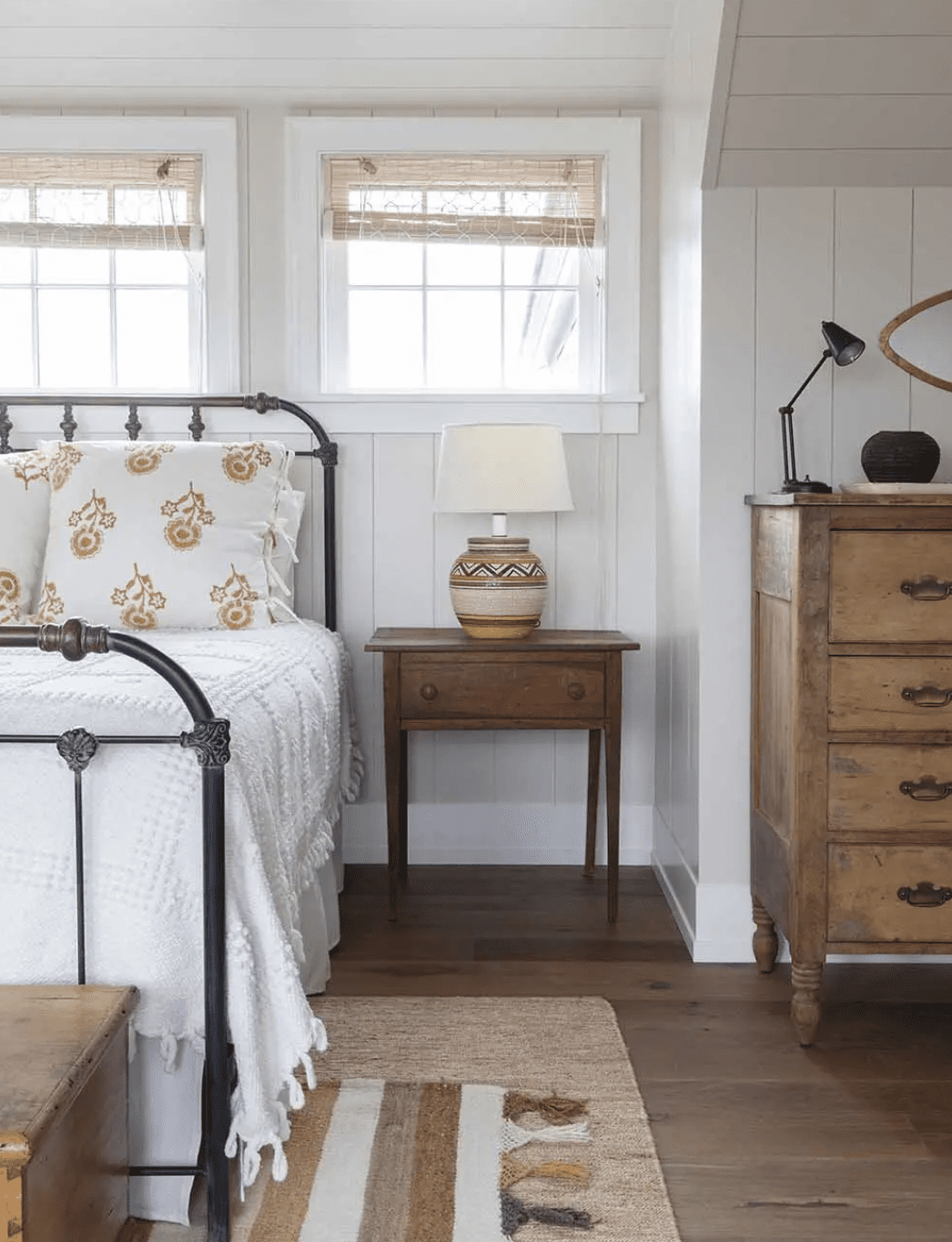 A bedroom filled with antique wood furniture and and traditional patterns (like stripes and florals)