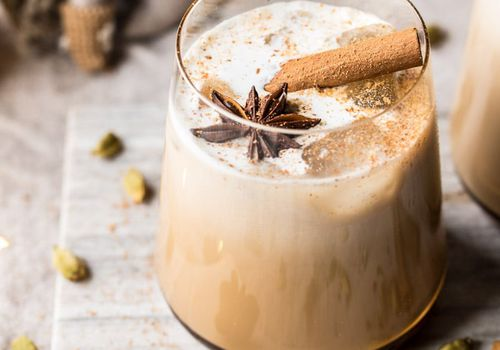 White Russian cocktail in a rocks glass with star anise and cinnamon stick garnish.