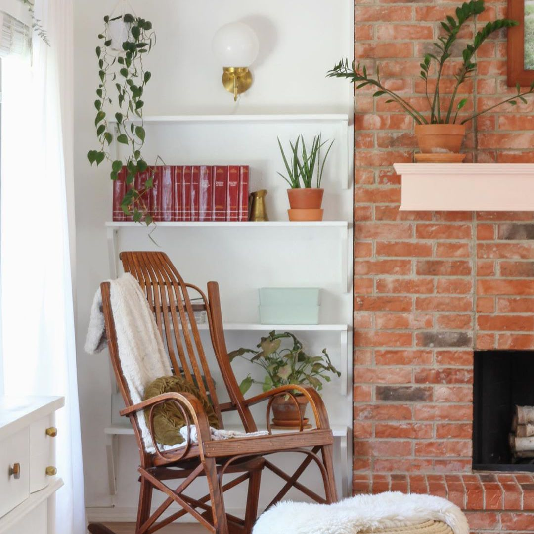 Rocking chair in family room by brick fireplace.