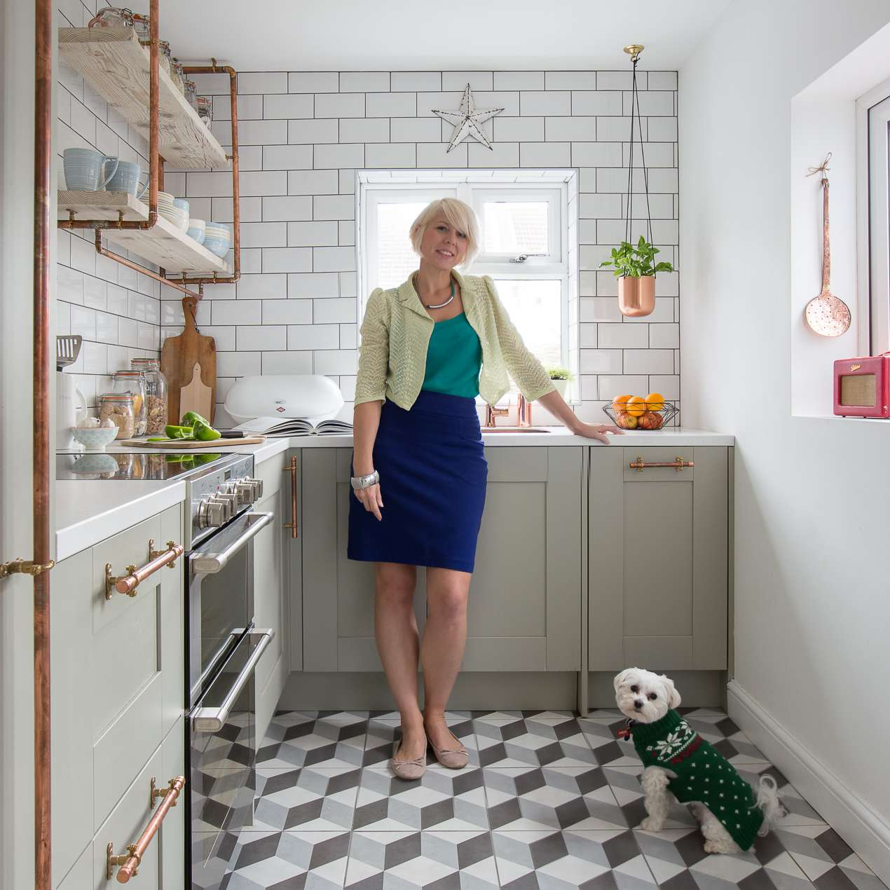 Maxine in her kitchen with dog and hanging plants.