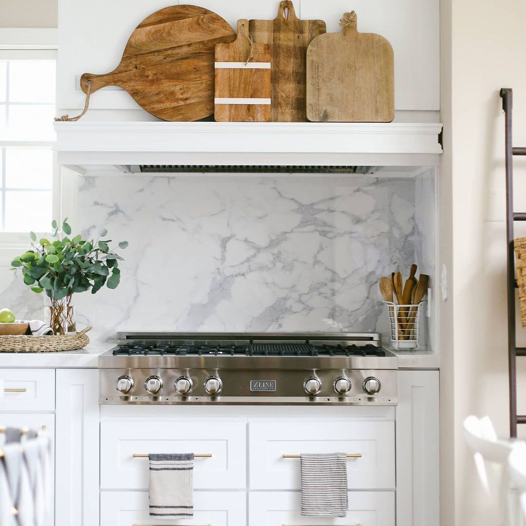 White kitchen with marble backsplash and vintage cutting board display