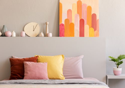 Colorful pillows on bed in grey bedroom interior with poster and clock on bedhead. Real photo