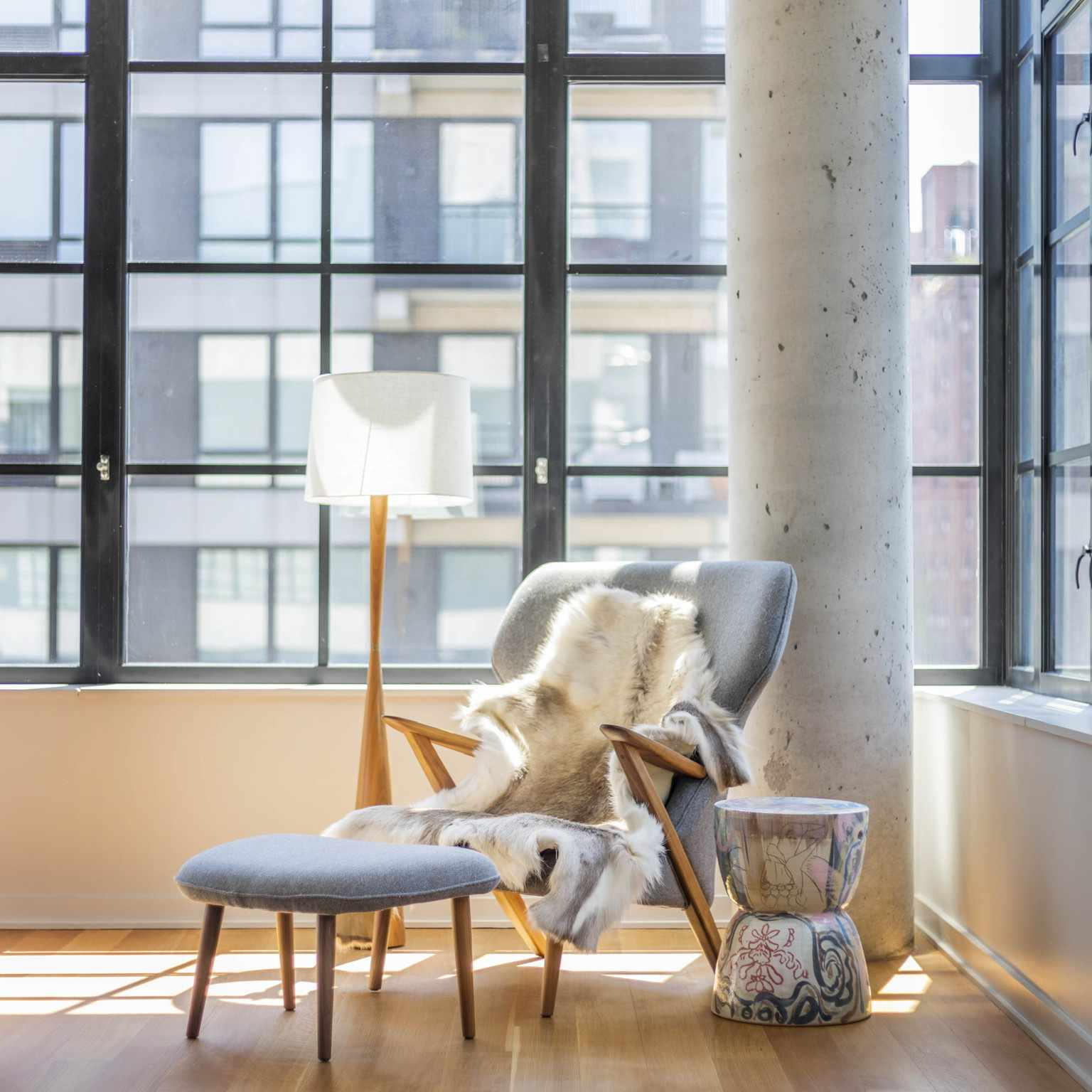 yael weiss nyc apartment - bedroom with floor to ceiling windows and reading chair
