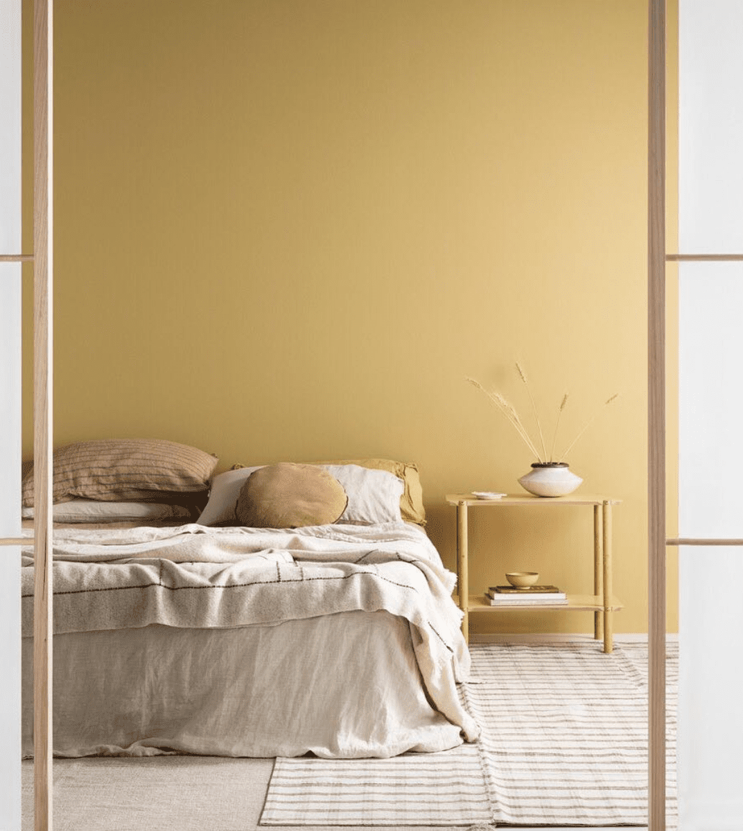 Clear entryway to minimalist bedroom in soft rolled hay yellows