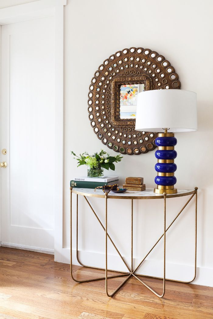 A half moon table, round mirror and stack of books topped with a potted plant in an entryway