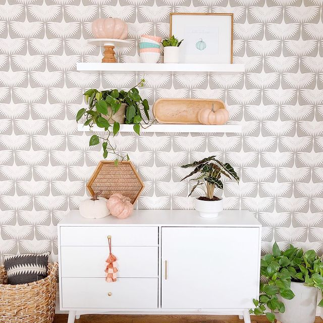 Alocasia Polly on a styled credenza against a wall papered wall