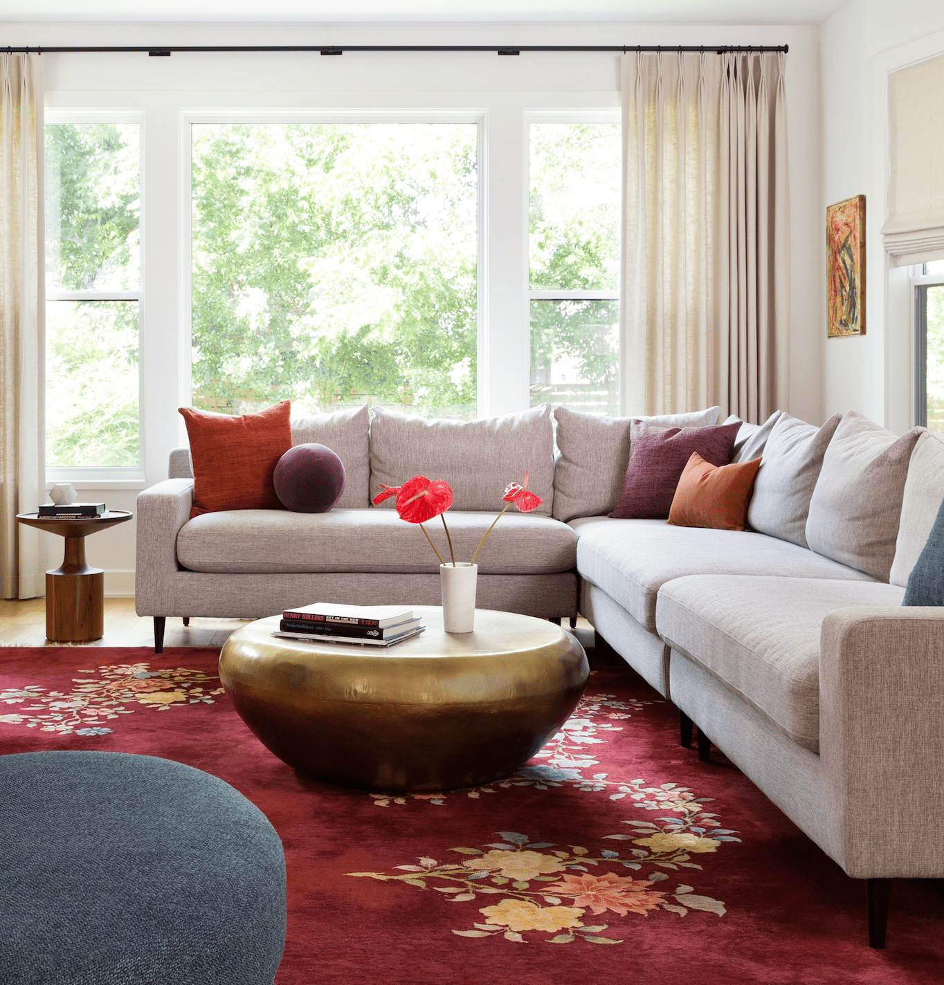 Bright vibrant living room with red rug and florals.