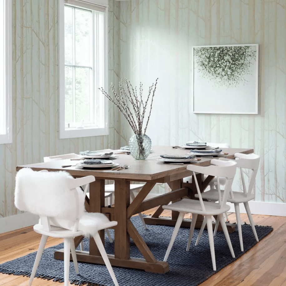 A dining room with light blue-green walls and a navy rug
