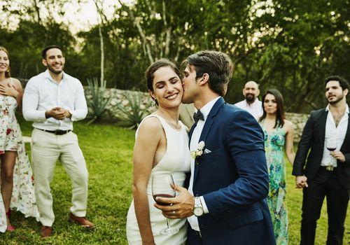 Pareja casada con invitados a la boda que les rodea.