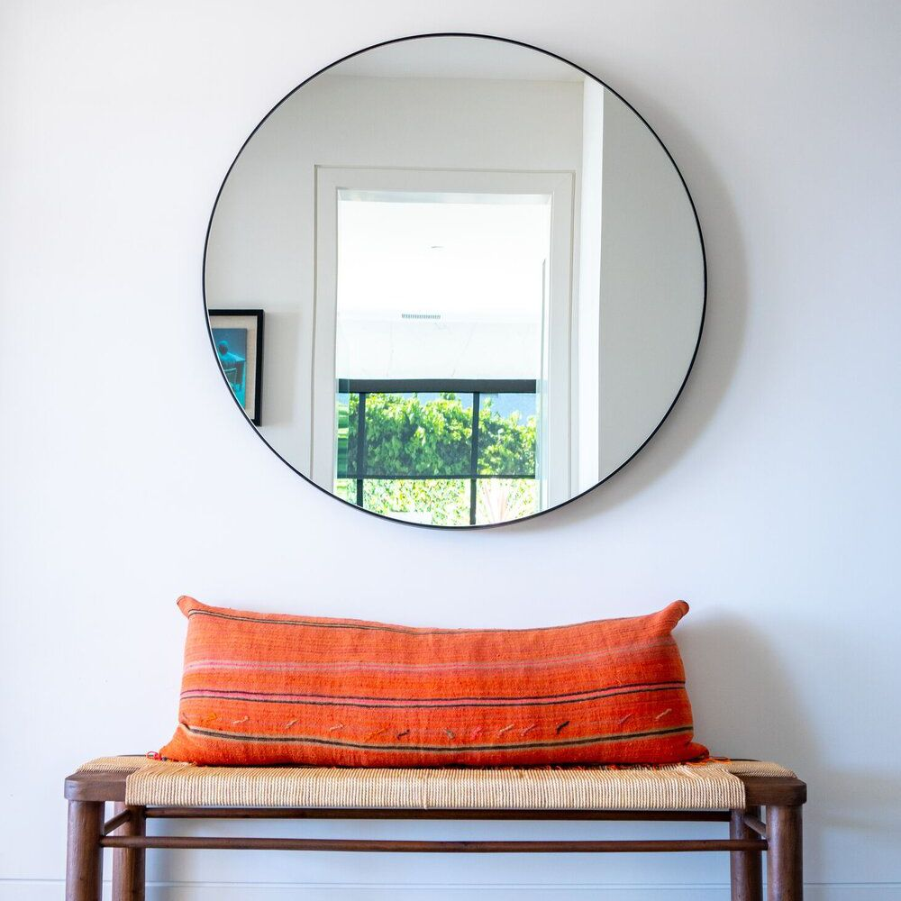 Bench in a foyer with a mirror above it