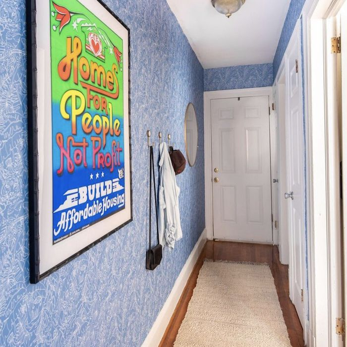 entryway with blue wallpaper, neon color poster, golden hooks, woven rug