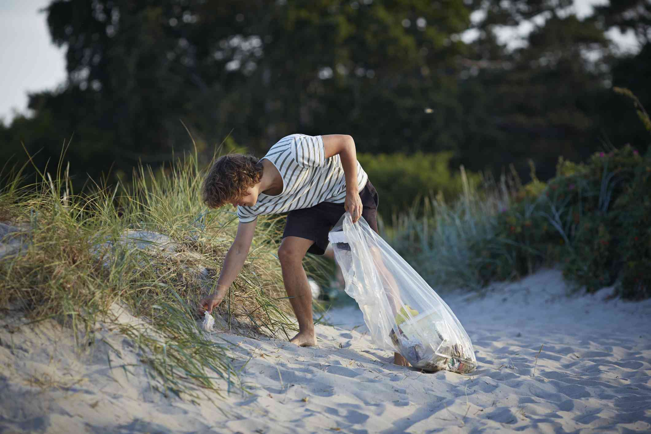 Young man picks up trash on the beach