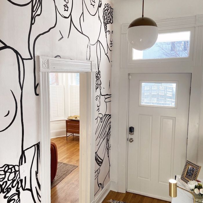 entryway with large mural of drawn people, small marble table by the door