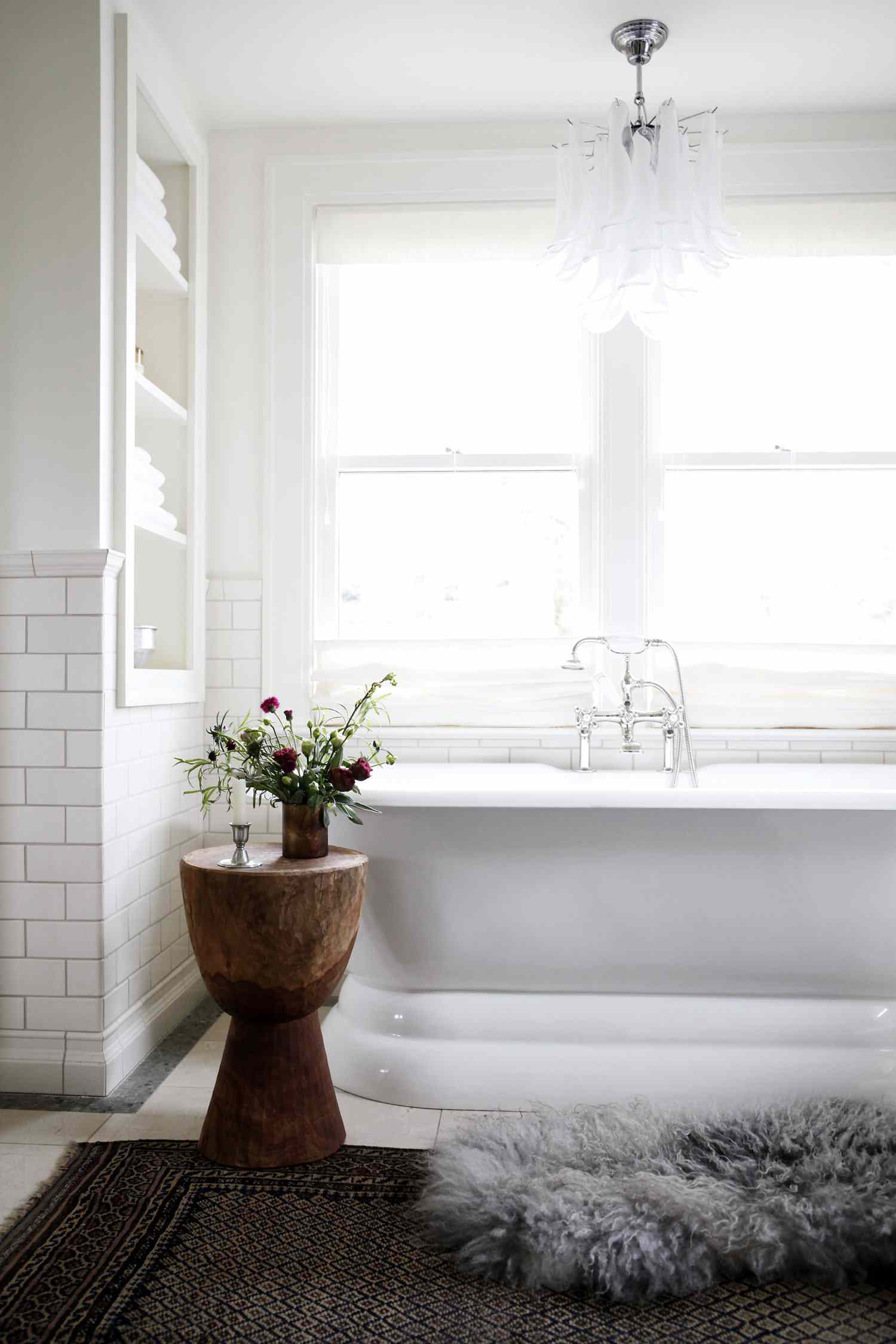 Tub nook with layered rugs and chunky wood side table