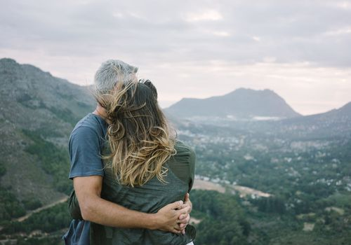 a couple overlooking a mountain hugging eachother