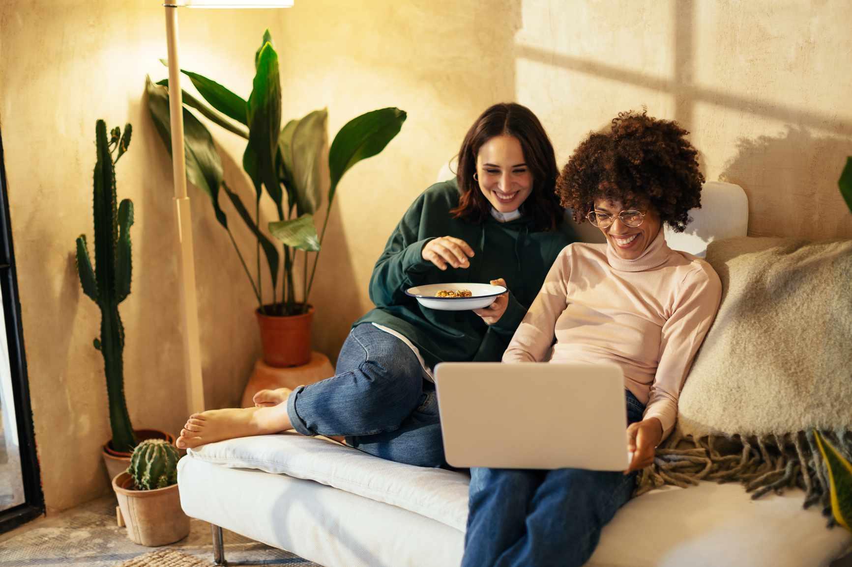 Two women watching TV on laptop.