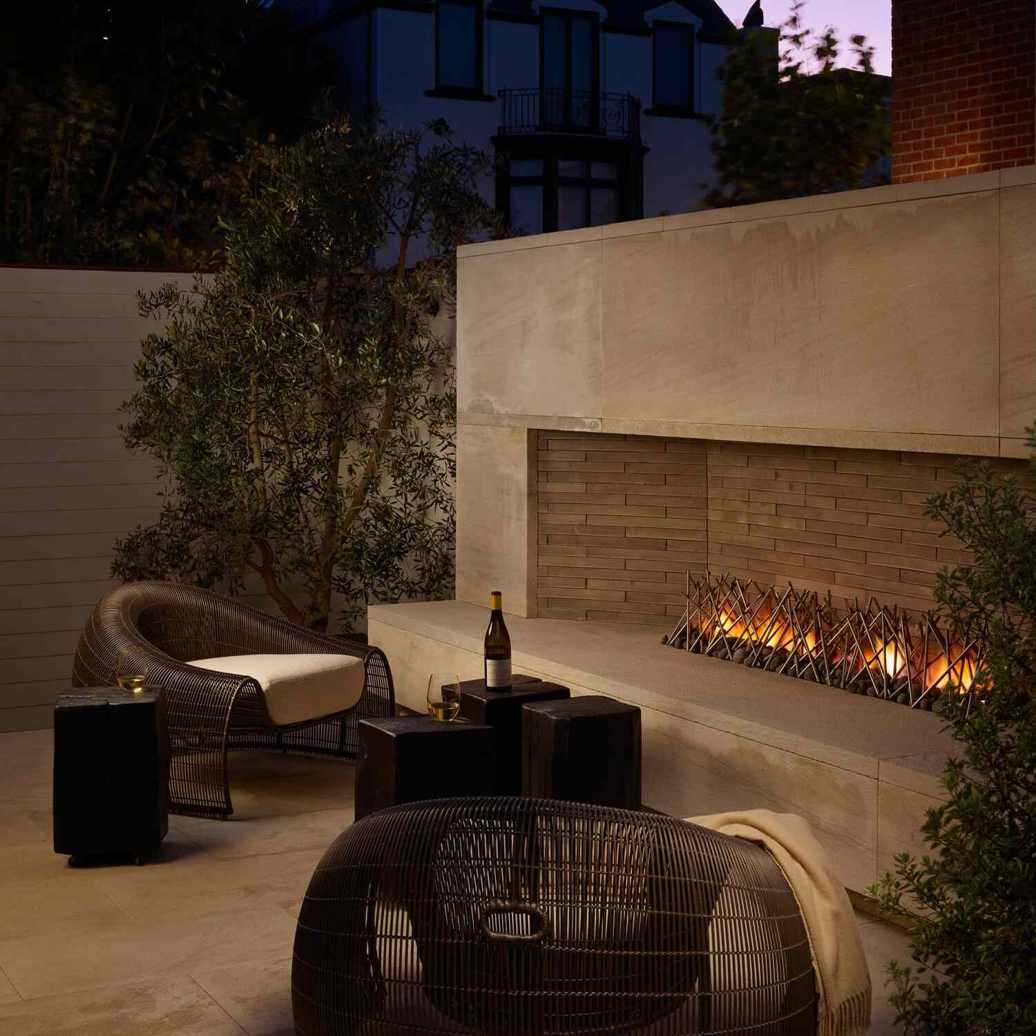 An outdoor fireplace filled with wire sticks, which are evoked by the wire-lined lounge chairs placed nearby