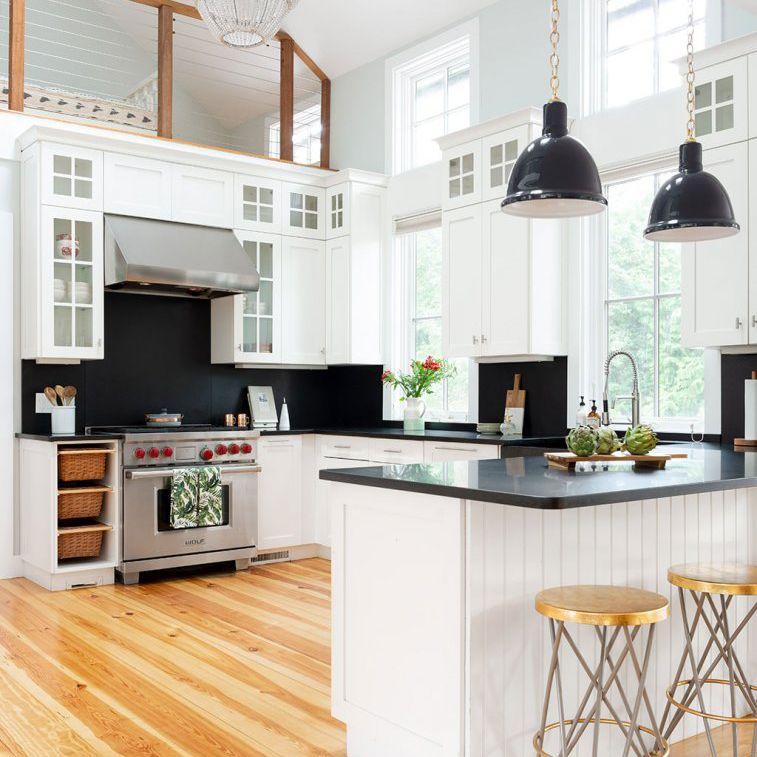 Minimalist kitchen with dark countertops and backsplash, chandelier