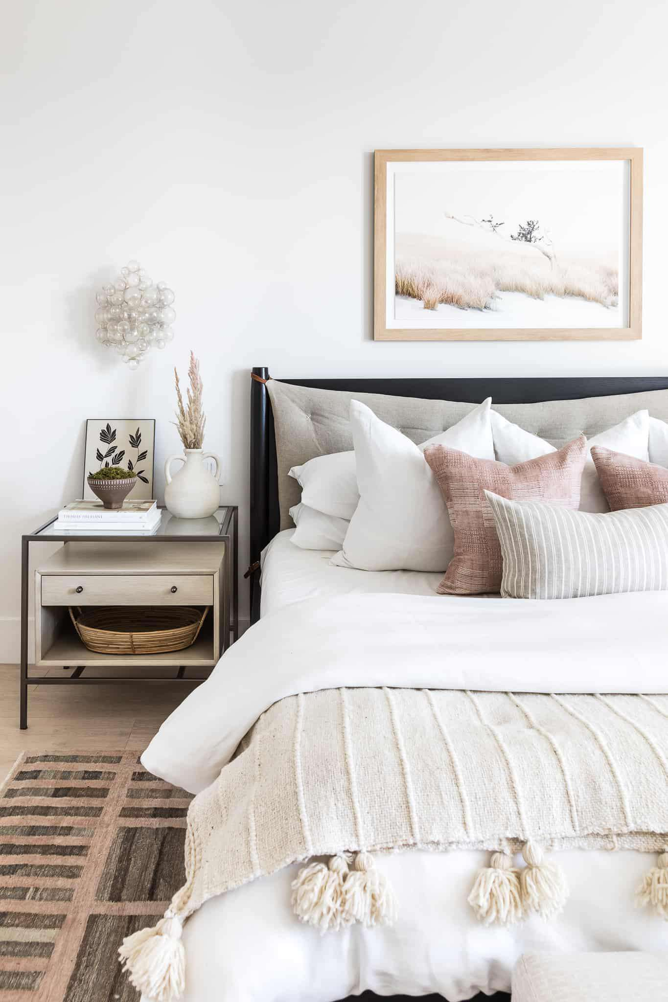 Soft neutral bedroom with dusty pink accents.