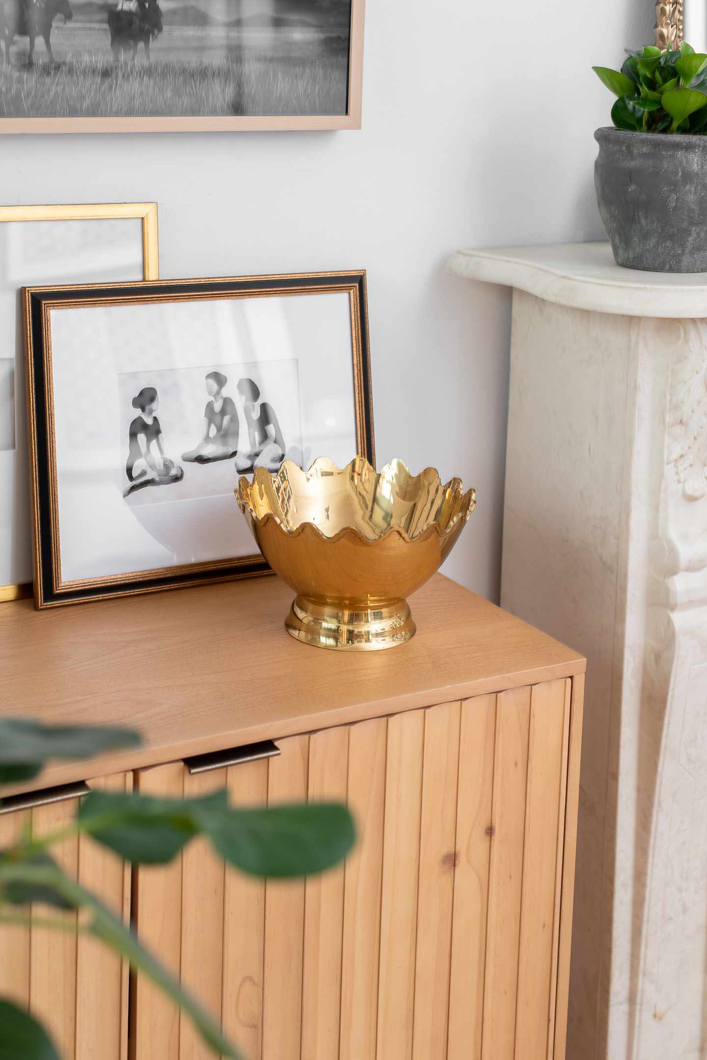 Wooden dresser with gold bowl on top.