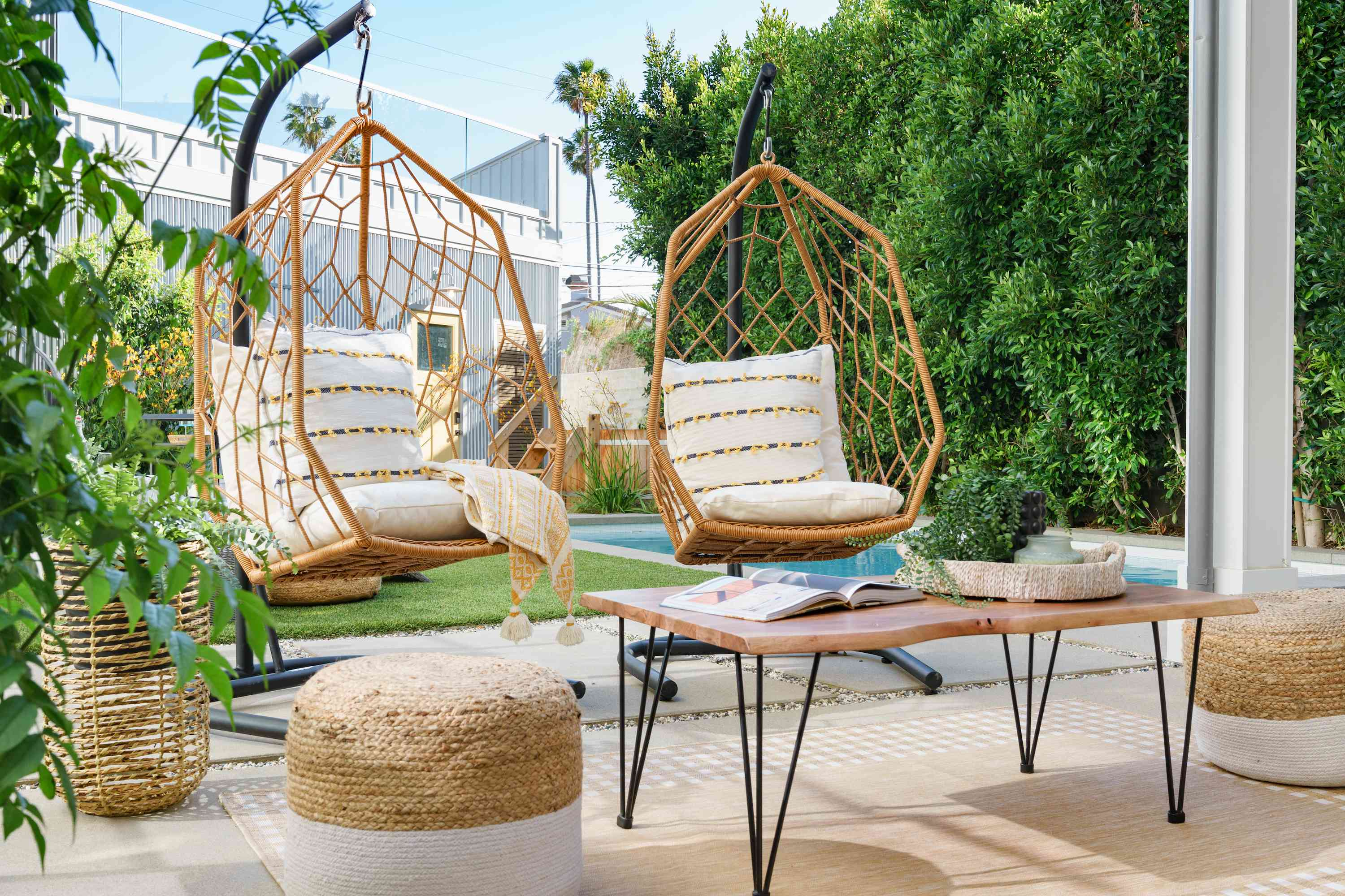 Two hanging rattan chairs outside.