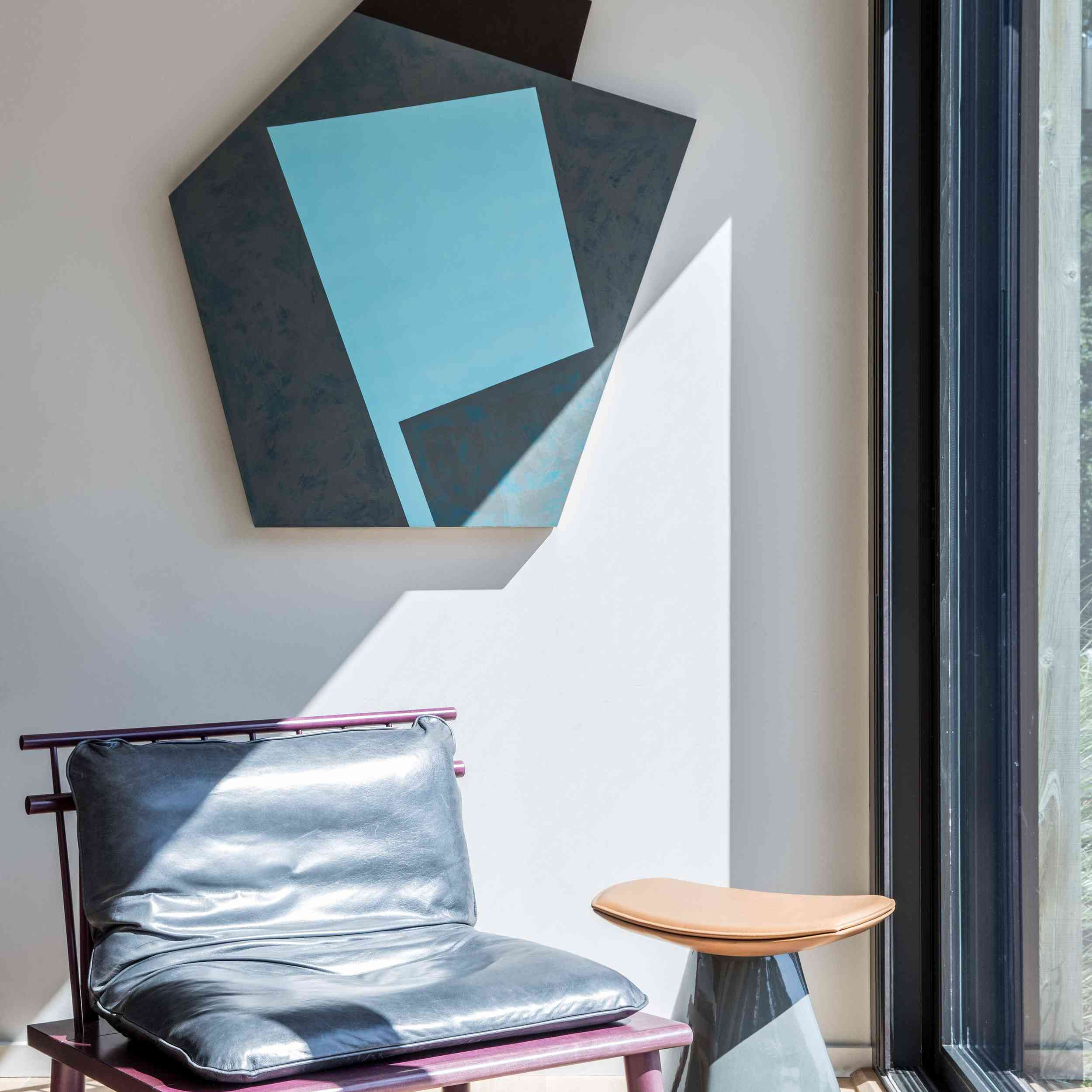 A room corner decorated with sleek furniture and modern art