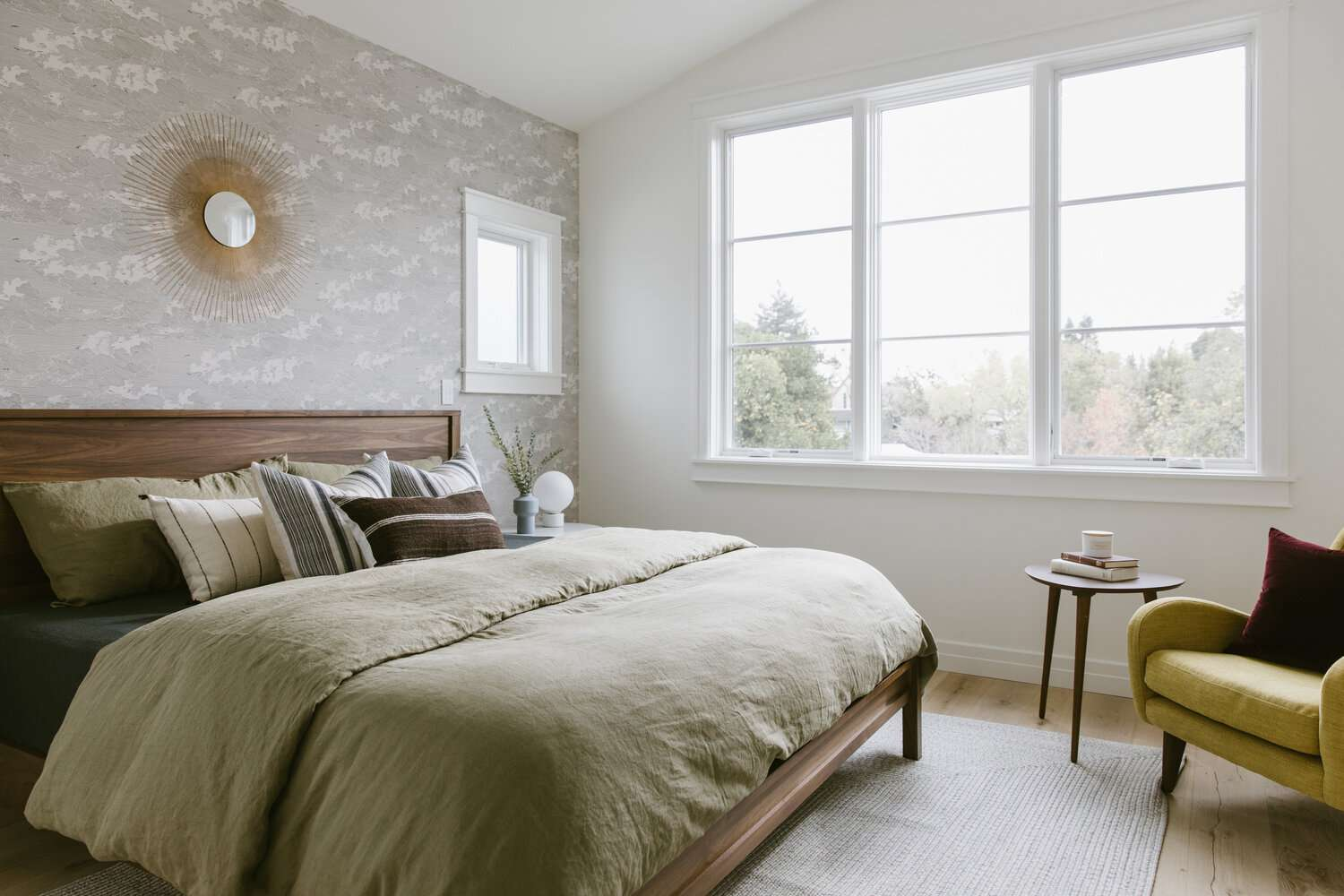 Modern bedroom with gray abstract wallpaper and green bedding
