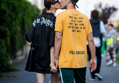 a couple kissing as they go for a walk