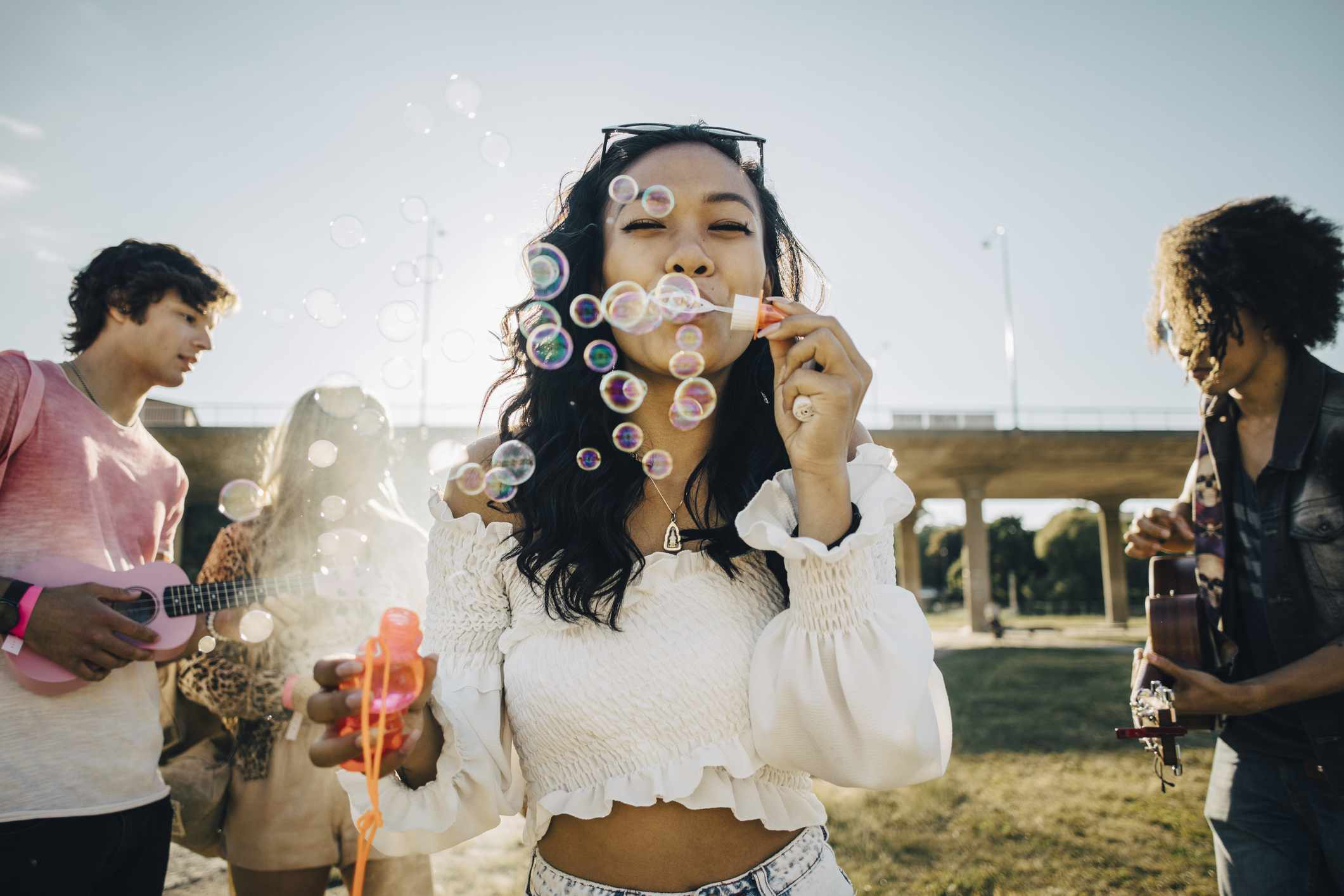 Young woman in crop top blows bubble at music festival
