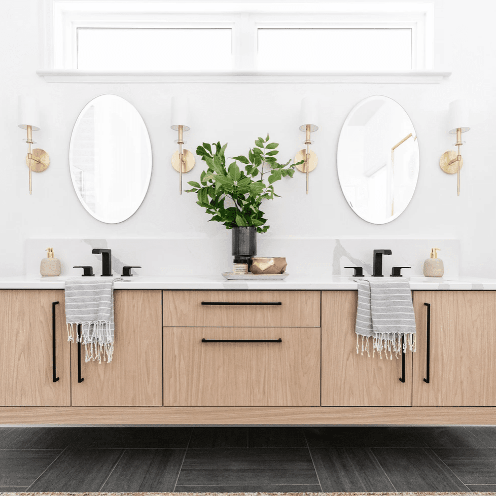 A double vanity made up of two oval mirrors and a hovering wooden cabinet