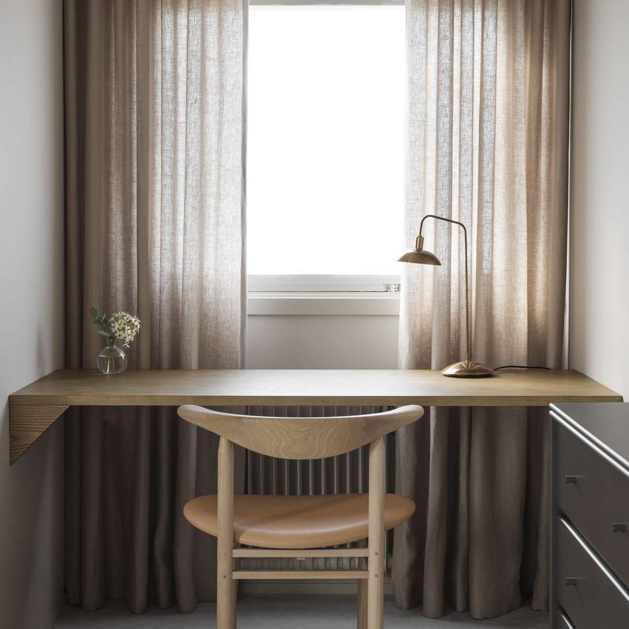 A small desk tucked against a curtain-lined window