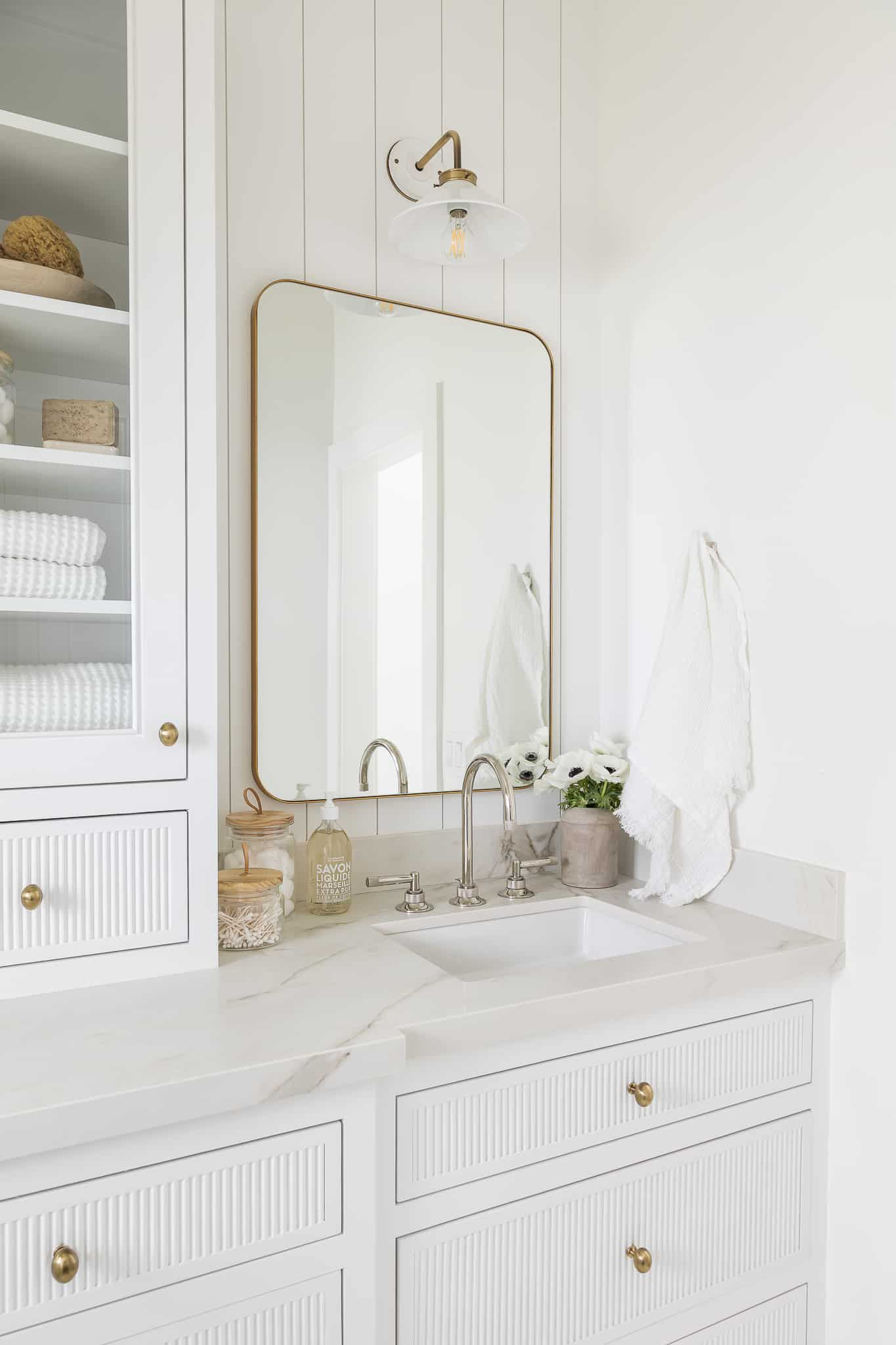 A small bathroom vanity equipped with shelves underneath and next to the sink