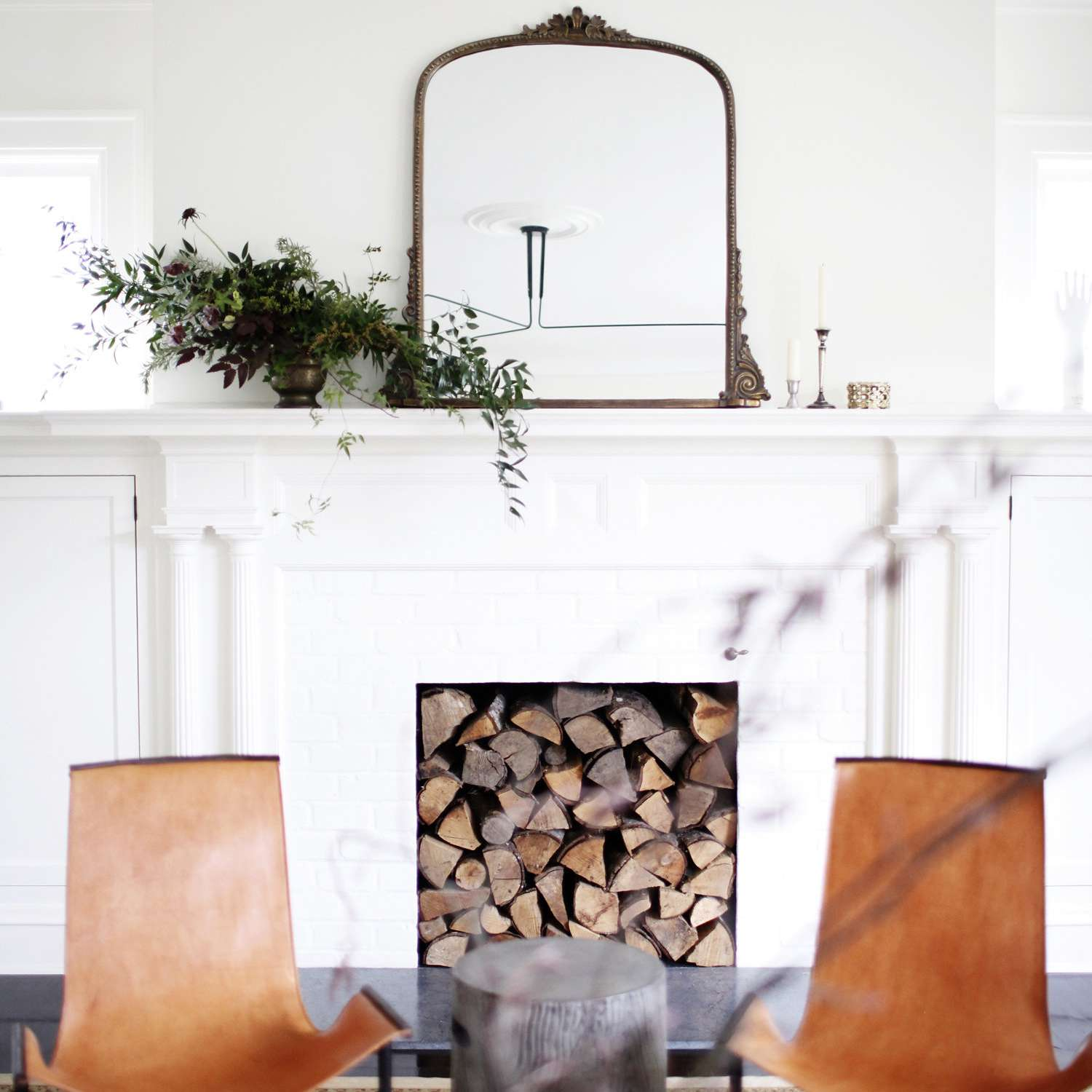 Bright and airy living room with traditional architecture and log-filled fireplace