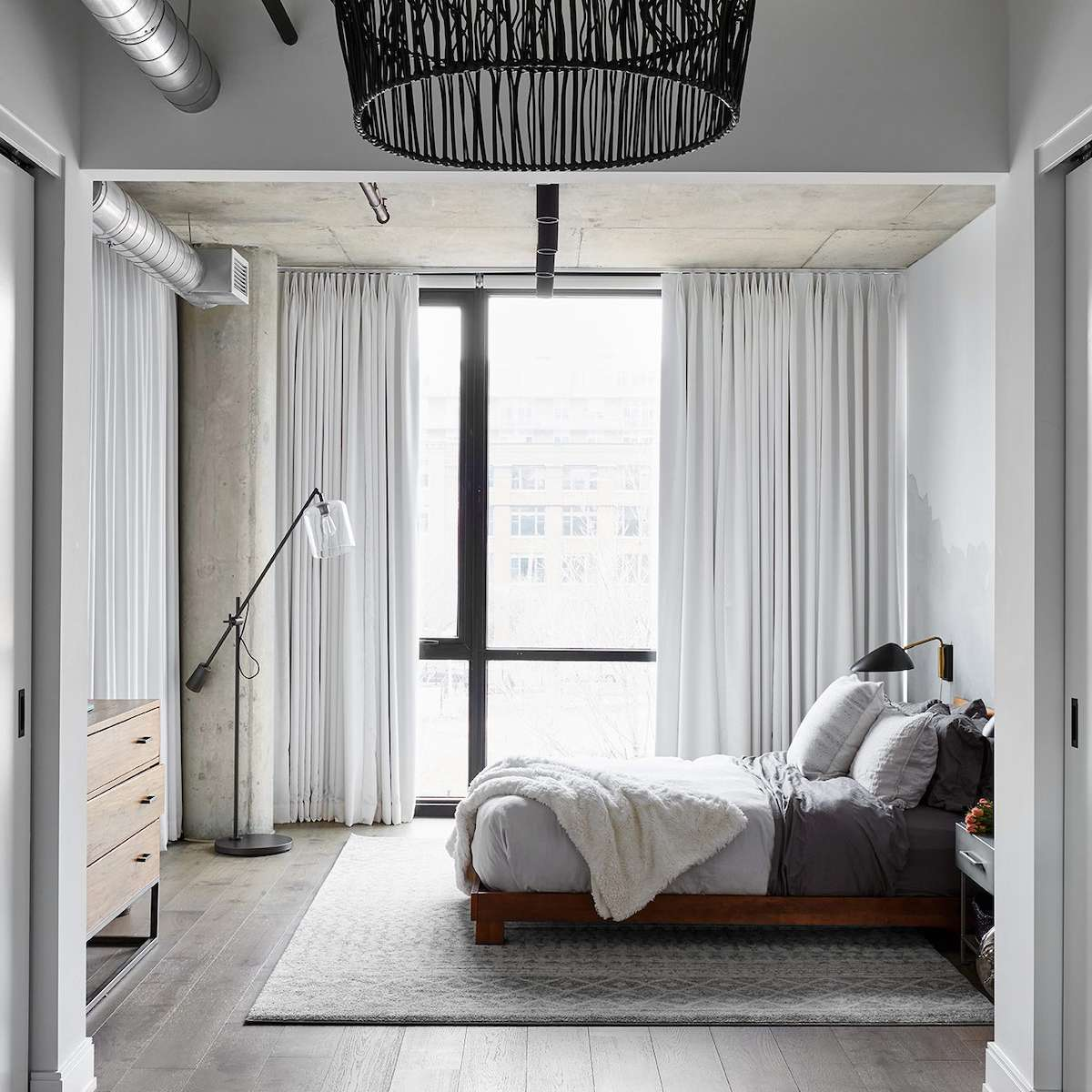 An industrial bedroom with a woven chandelier, a modern sconce, and an industrial floor lamp