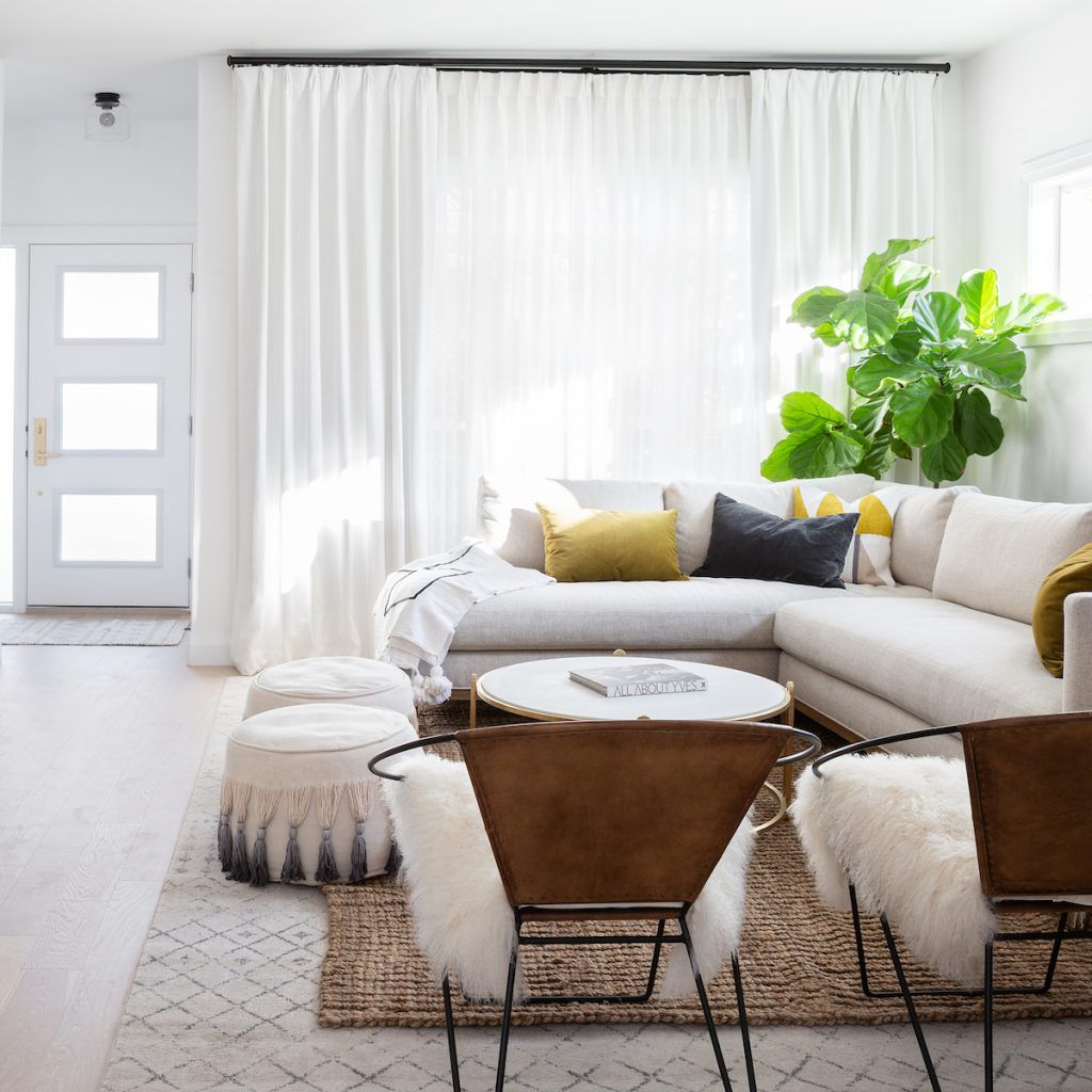 Bright, modern living room with sofa, chairs, and poufs.