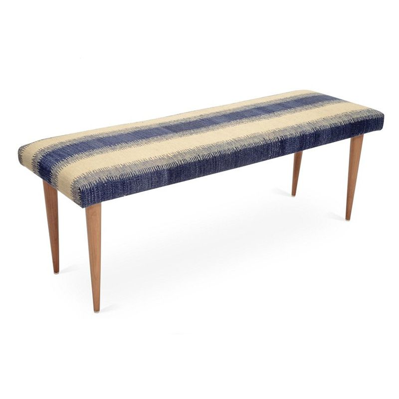 A bench upholstered in a blue striped kilim.