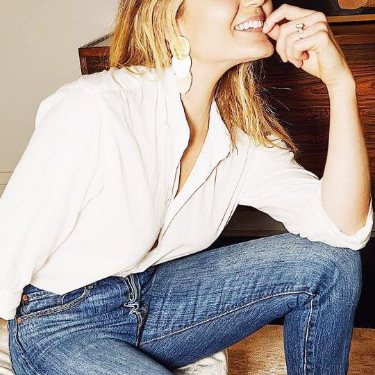 Young woman in white button-down shirt and jeans sits with eyes closed, smiling
