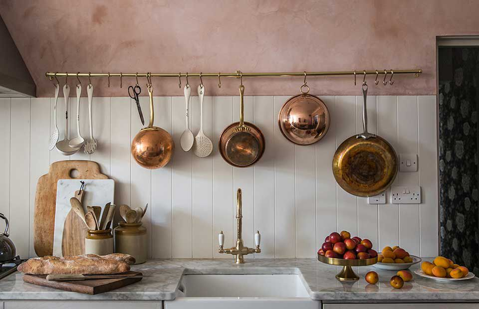 A kitchen with pink walls and rose gold pans hanging over the sink