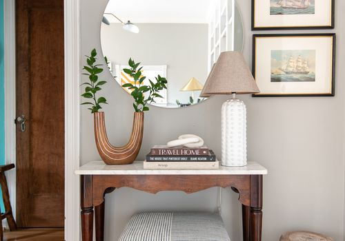 Inviting entryway with large mirror and ottoman.