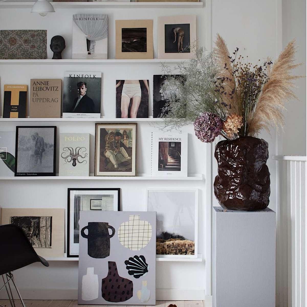 thin white floating shelves displaying various magazine