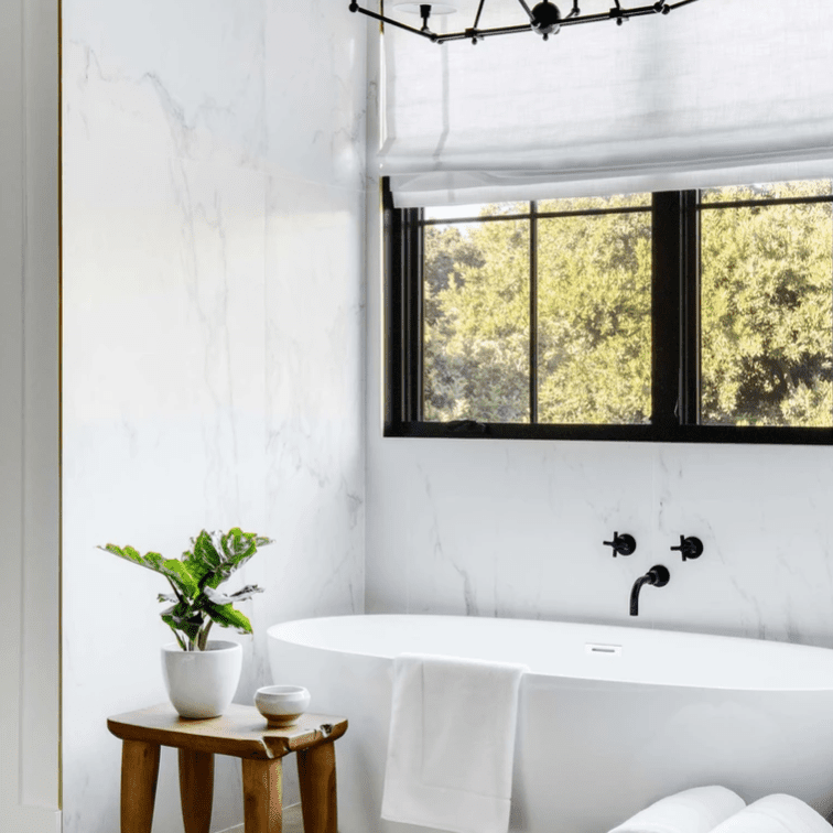 An all-white bathroom with a few vibrant brown touches