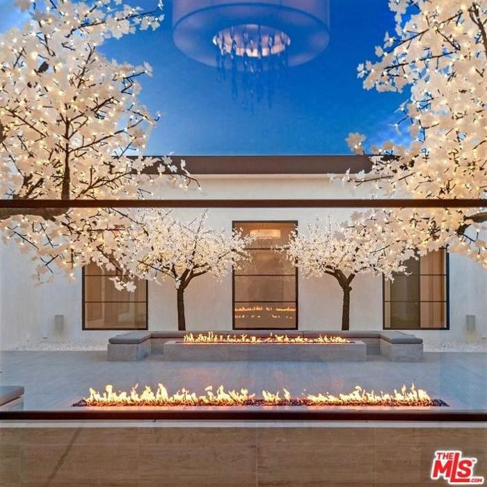 Lighted artificial trees with two long fire tables, outside of a large white home.