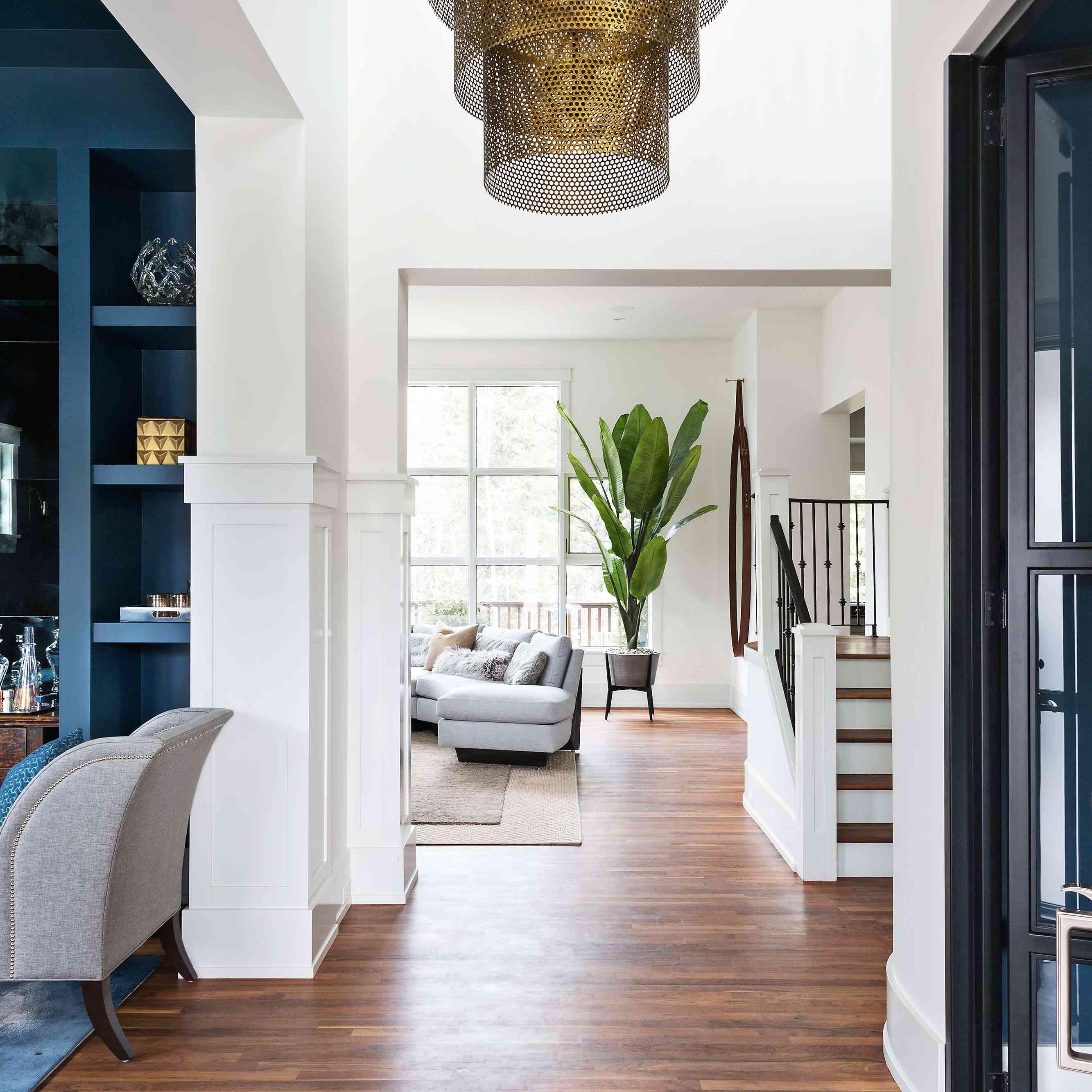 Foyer with beige runner, tiered-drum chandelier
